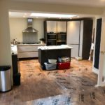 View of modernised kitchen with wooden tile flooring covered in plastic protective layers