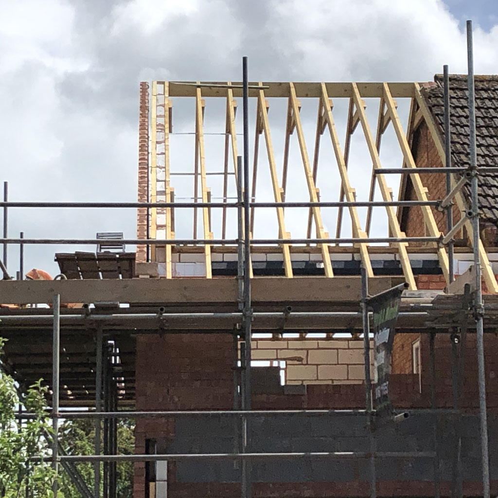 wooden frame of roof with bricks being laid held by scaffolding