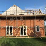 New build house surrounded in scaffolding and new wooden structure for roof being made