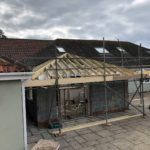 wooden frame of roof being built held by scaffolding