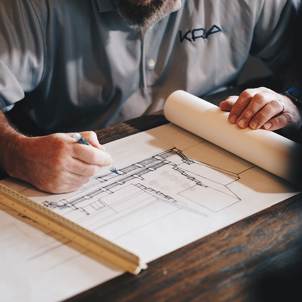 Man drawing up architecture sketch on paper against a wooden table