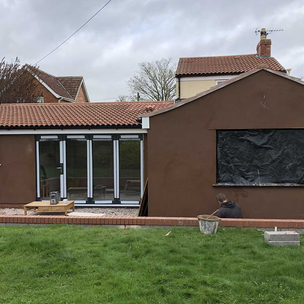 builder working on a brown house with a four panel glass door