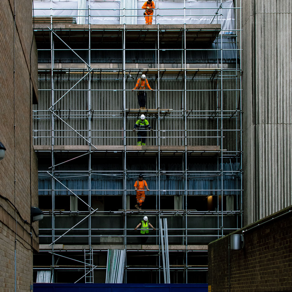 4 builders lined up vertically on each level of a large building with scaffolding
