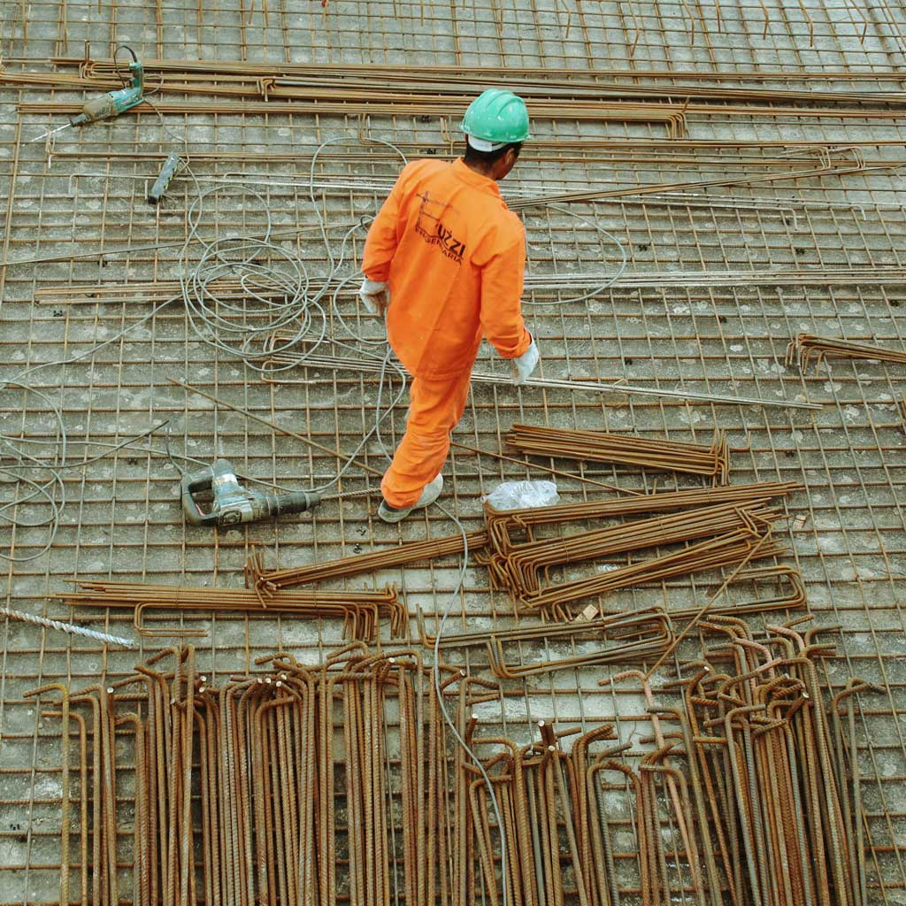 man-in-oragne-overalls-with-building-equipment-laid-out-on-ground